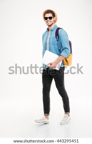 Full length of cheerful young man with backpack walking and holding laptop over white background - stock photo
