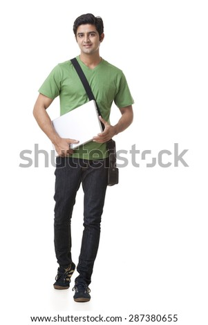 full length of college student with laptop walking over white background - stock photo