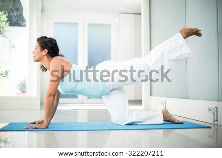 Full length of confident pregnant woman performing yoga on mat at fitness studio - stock photo