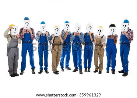 Full length of construction workers hiding faces with question mark signs against white background - stock photo