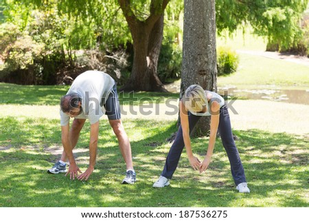 Full length of couple exercising together in the park - stock photo