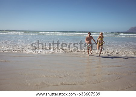 Full length of couple running on shore at beach during sunny day