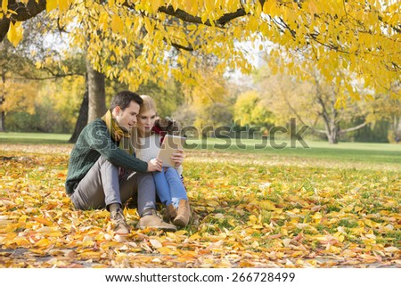 Full length of couple using tablet PC in park during autumn - stock photo
