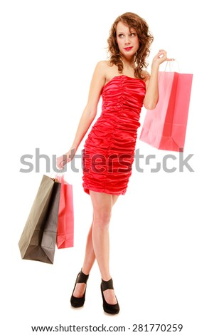 Full length of elegant girl young woman in red dress with paper shopping bags isolated on white. Sale and retail. Studio shot.