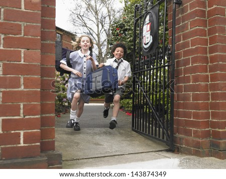 Full length of elementary students running out through school gate - stock photo