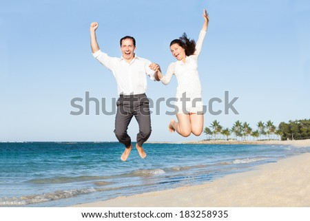 Full length of excited couple holding hands while jumping at beach - stock photo