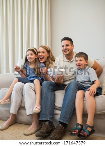 Full length of excited family watching television while sitting on sofa at home - stock photo