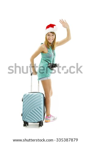 Full length of excited traveler in santa hat with camera and suitcase going on vacation. - isolated on white background  - stock photo