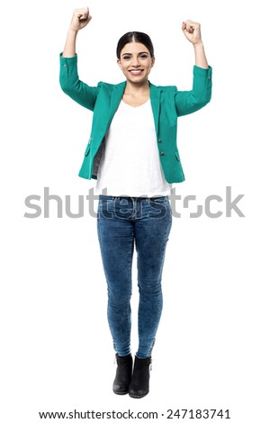 Full length of excited woman keeping arms raised - stock photo