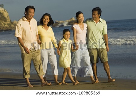 Full length of family and friends walking together on beach - stock photo