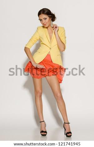 Full length of fashion model posing in mini skirt fluttering on the wind - stock photo