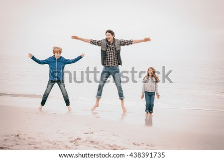 Full length of father enjoying with children at sea shore against sky - stock photo