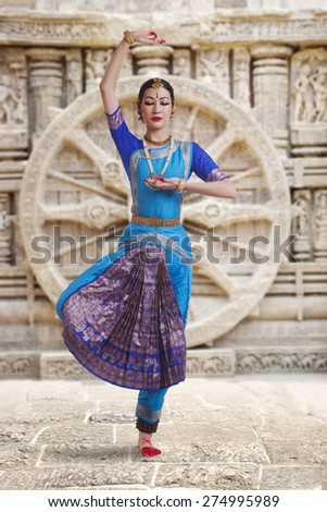 Full length of female Bharat Natyam dancer performing against carved wall - stock photo