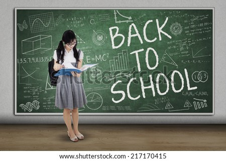 Full length of female college student standing in class while holding document - stock photo