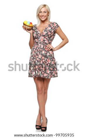 Full length of female fashion model holding basket with Easter eggs, isolated on white background
