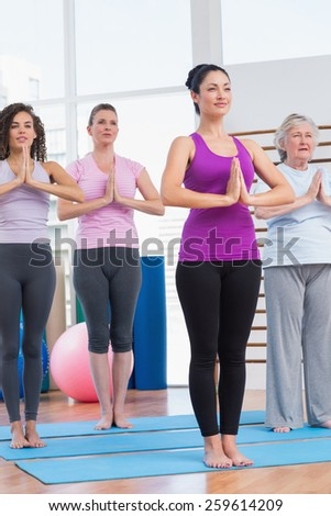 Full length of female friends with hands clasped exercising in gym - stock photo