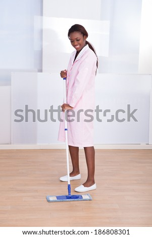 Full length of female housekeeper mopping floor in hotel - stock photo