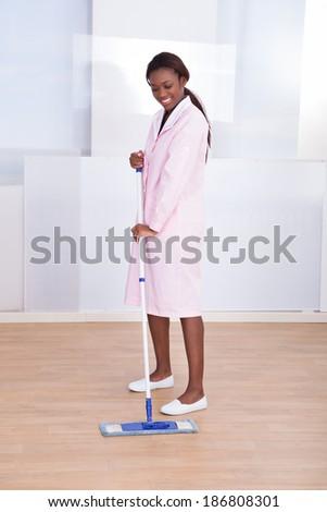 Full length of female housekeeper mopping floor in hotel - stock photo