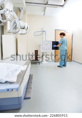 Full length of female nurse adjusting xray film in machine at examination room - stock photo
