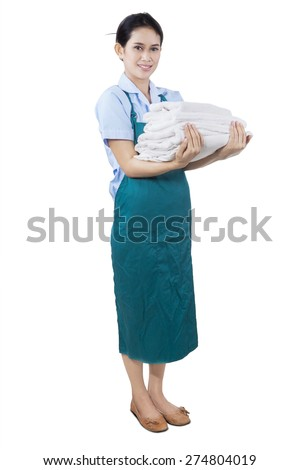 Full length of female young maid wearing apron while holding bedding and towels, isolated on white background - stock photo