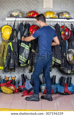 Full length of firefighter removing uniform hanging at fire station - stock photo