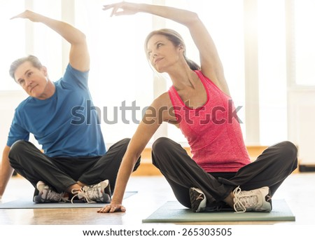 Full length of fit mature couple practicing yoga on mat at home - stock photo
