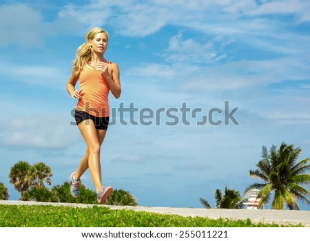 Full length of fit young female athlete jogging on footpath against sky - stock photo