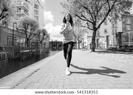 Full length of fit young woman jogging by canal against buildings