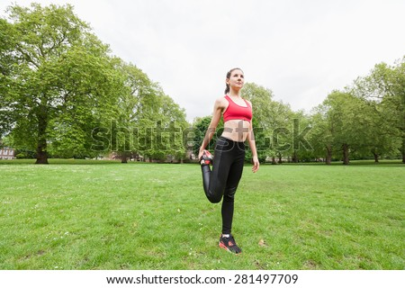 Full length of fit young woman performing stretching exercise in park