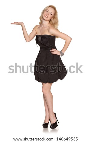 Full length of flirtatious woman with radiant smile showing copy space on her palm, looking at camera, isolated on white background - stock photo