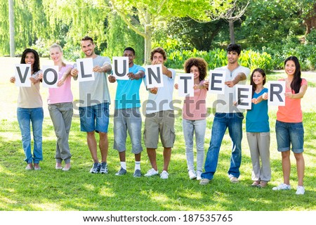 Full length of friends holding placards spelling volunteer on campus - stock photo