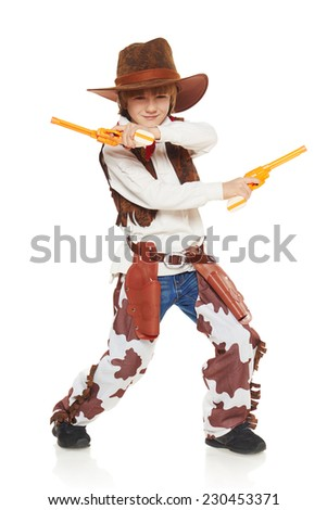 Full length of funny furious little boy in a suit of the cowboy holding guns, on a white background - stock photo