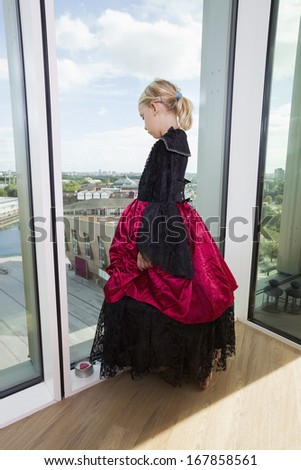 Full length of girl in vampire costume looking out through window at home - stock photo