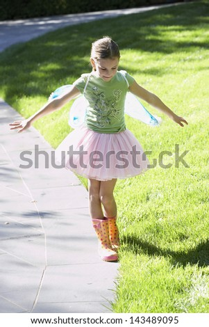 Full length of girl wearing fairy wings and tutu balancing on edge of path at park - stock photo