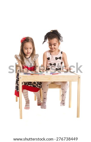 Full length of girls sitting at table and drawing together isolated on white background - stock photo