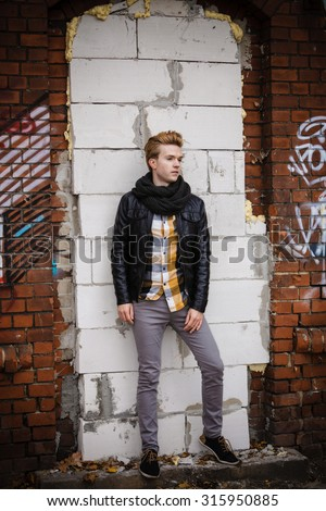 Full length of handsome trendy man outdoor in city setting, male model wearing black jacket scarf and checked shirt against brick wall - stock photo