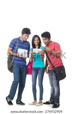 Full length of happy college students using digital tablet over white background - stock photo