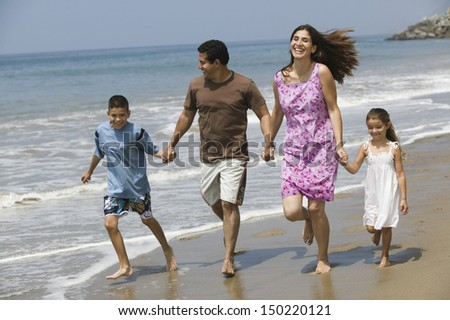 Full length of happy family holding hands while running on beach - stock photo