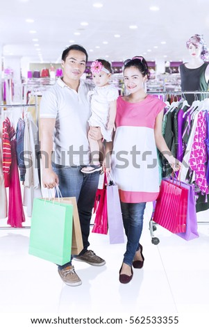 Full length of happy family shopping together while standing in fashion store