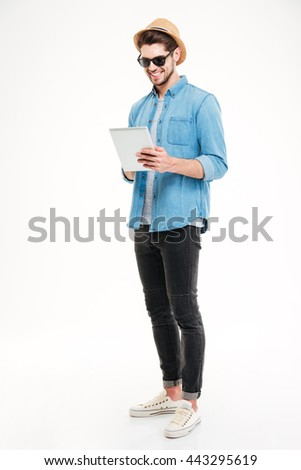 Full length of happy handsome young man using tablet over white background - stock photo