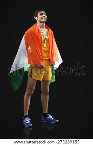 Full length of happy male medalist with Indian flag looking away against black background - stock photo