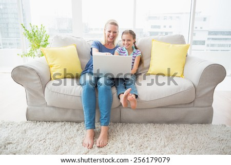 Full length of happy mother and daughter using laptop on sofa at home - stock photo