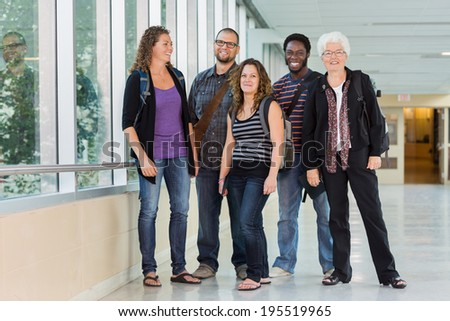 Full length of happy multiethnic university students standing at corridor - stock photo