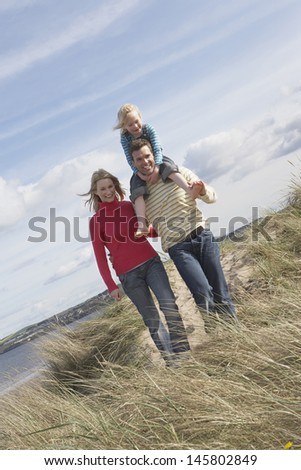 Full length of happy parents with daughter walking on beach - stock photo