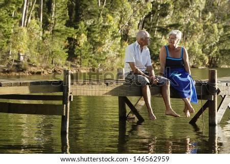Full length of happy senior couple sitting on pier at lake - stock photo