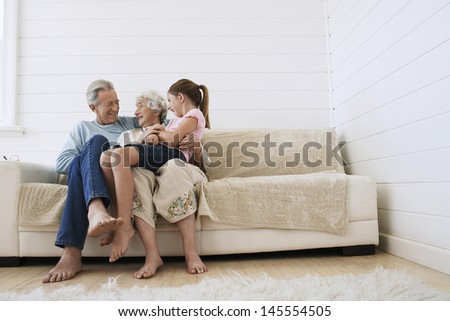 Full length of happy senior couple sitting with granddaughter on couch