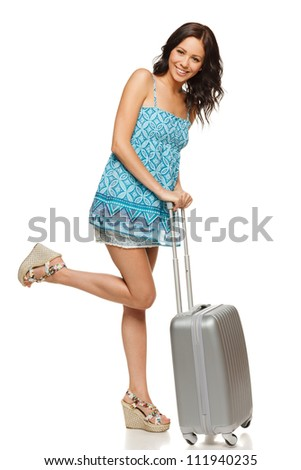 Full length of happy smiling casual female standing with travel suitcase, isolated on white background