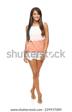 Full length of happy smiling funky young female in summer shorts and top with blue hair lock coloring walking over white background - stock photo