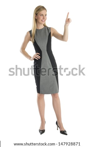 Full length of happy young businesswoman with hand on hip pointing upwards isolated over white background
