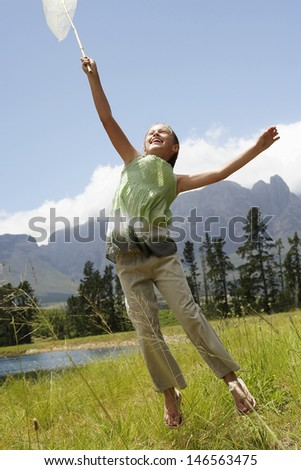 Full length of happy young girl with butterfly net jumping in field - stock photo